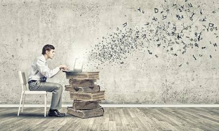 Junger Mann sitzt in einer irrealen Szene an einem zum Tisch gestapelten Bücherberg und tippt